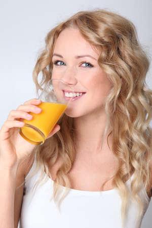 Blond woman drinking orange juice photo