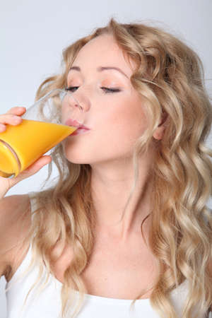 Blond woman drinking orange juice photo