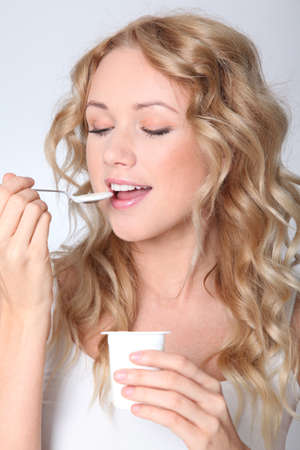 Portrait of woman eating yogurt photo
