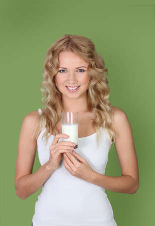 Portrait of woman holding glass of milk on green background