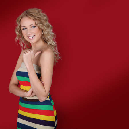 Beautiful blond woman showing thumb up on red background photo