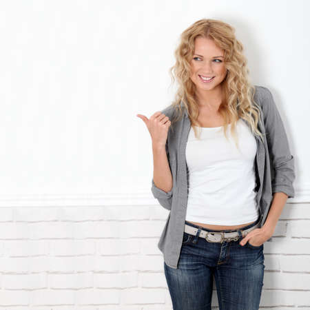 woman pointing up: Beautiful blond woman showing thumb up