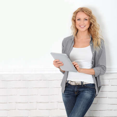 standing against: Beautiful modern woman using digital tablet