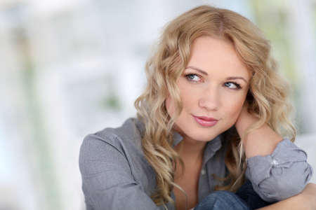 blonde  blue eyes: Portrait of beautiful blond woman relaxing at home