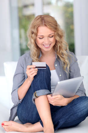 Blond woman doing online shopping with digital tablet photo