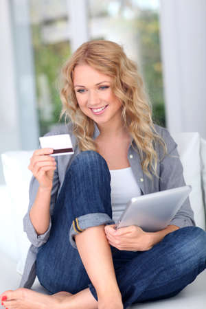 secured payment: Blond woman doing online shopping with digital tablet