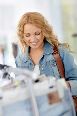 Beautiful blond woman looking at price tags in store photo