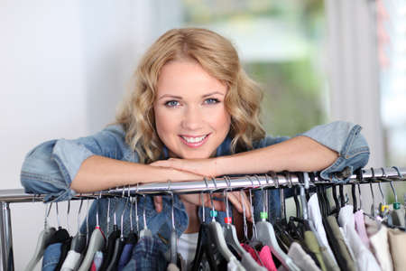 Portrait of blond woman leaning on clothes hanger photo