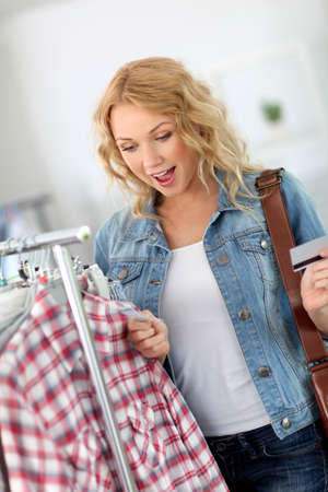 Attractive woman in clothing store checking price photo