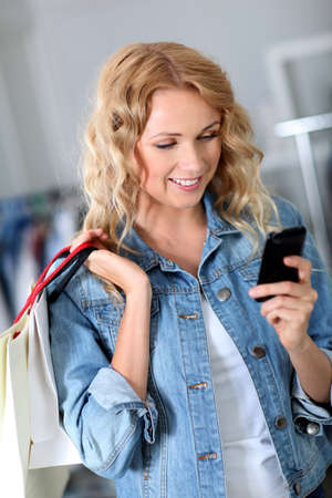 Woman using mobile phone while shopping photo