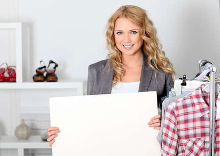 shop tender: Beautiful woman in garment store holding message board Stock Photo