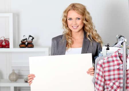 shopgirl: Beautiful woman in garment store holding message board Stock Photo