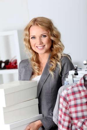 shoe boxes: Mujer atractiva llevando cajas de zapatos en la tienda