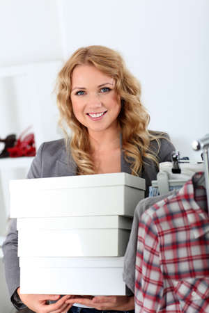 Attractive woman carrying shoe boxes in store photo