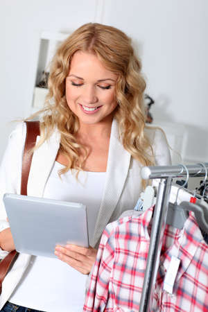 Beautiful woman in garment store using electronic tablet photo