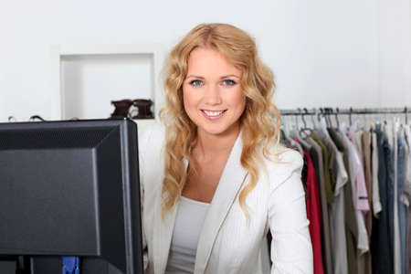 saleswomen: Beautiful shop tender standing by cash register Stock Photo