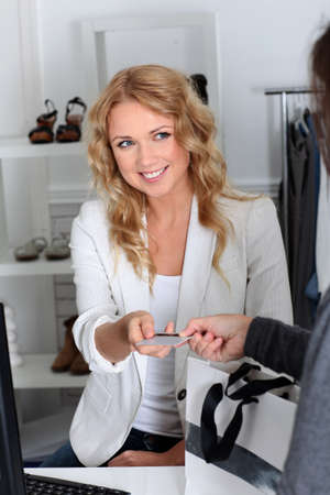 saleswomen: Customer in retail store paying with credit card Stock Photo