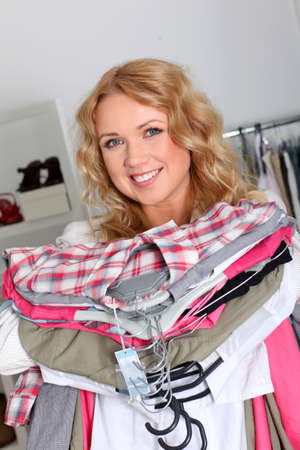 Woman in garment store holding pile of clothes photo