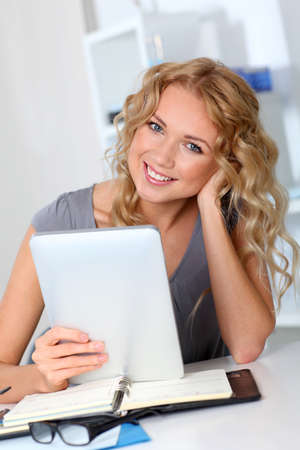 Beautiful woman in office using digital tablet photo