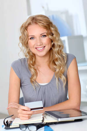 virtual assistant: Beautiful woman doing online shopping in office Stock Photo