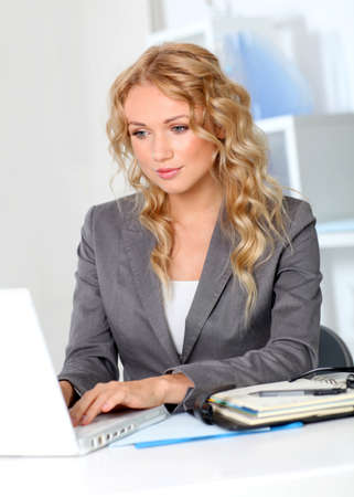 executive assistants: Portrait of businesswoman in office working on laptop computer