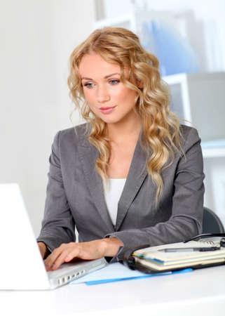 typing: Retrato de la empresaria en la oficina de trabajo en la computadora port�til Foto de archivo