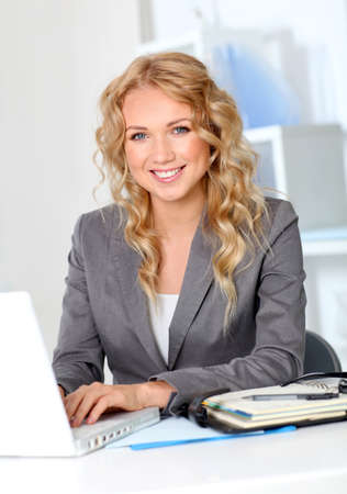 officeworker: Portrait of businesswoman in office working on laptop computer