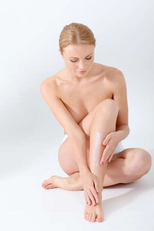 Beautiful woman applying moisturizer on her legs photo