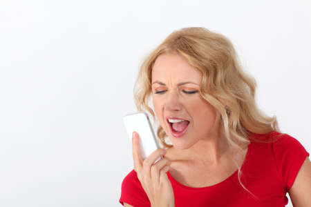Portrait of blond woman with red shirt yelling on the phone photo