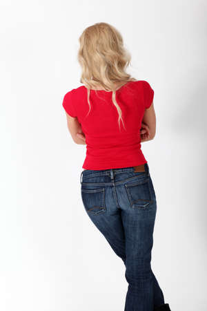 red jeans: back view of woman with red shirt Stock Photo
