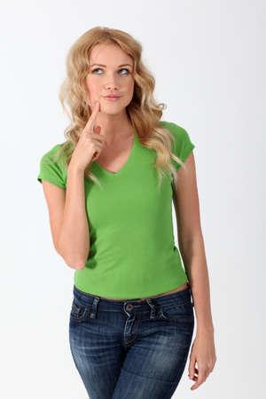 questionnement: Femme blonde avec chemise verte ayant regard pensif