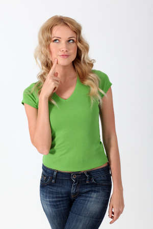 interrogativa: Mujer rubia con camisa verde con mirada pensativa Foto de archivo