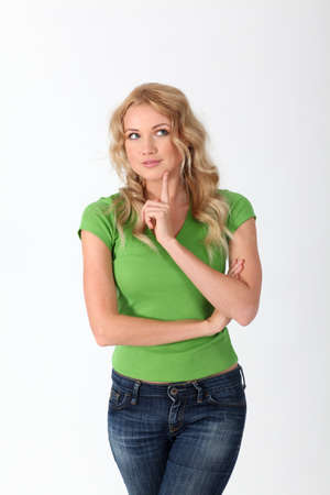 Blond woman with green shirt having thoughtful look photo