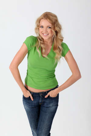 Beautiful smiling woman in green shirt with hands in pockets photo