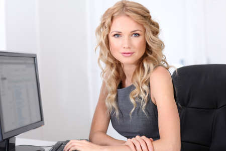 secretary desk: Smiling businesswoman at work in office