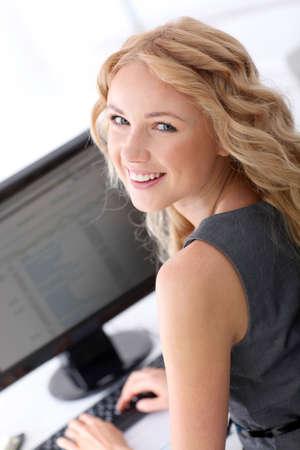secretary desk: Smiling businesswoman at work in ofice Stock Photo