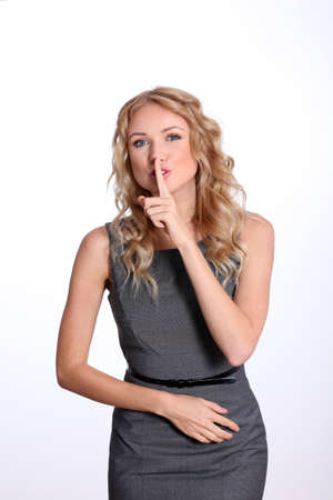Businesswoman with finger on mouth to be quiet photo
