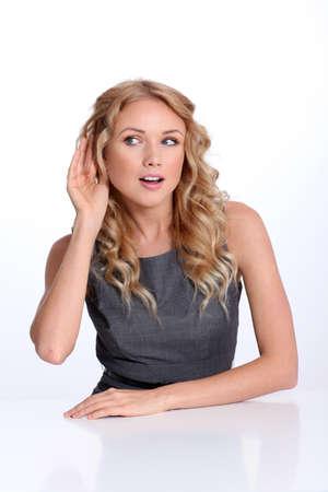 actief luisteren: Zakenvrouw met de hand op het oor te luisteren Stockfoto