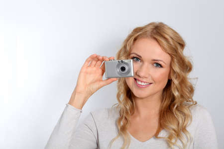 Portrait of beautiful blond woman taking picture photo