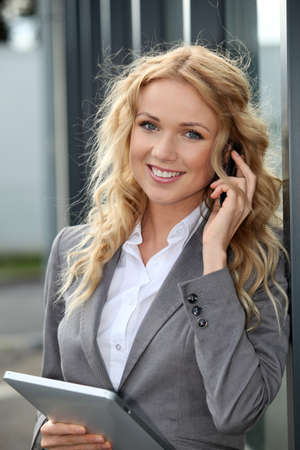 Saleswoman using mobile phone and digital tablet photo