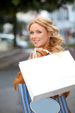 closeup on bags: Beautiful woman in town holding shopping bags
