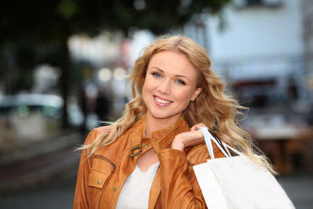 Beautiful woman in town holding shopping bags photo
