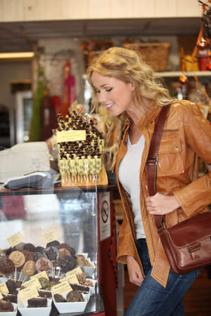craving: Woman looking at chocolate and treats by shopwindow