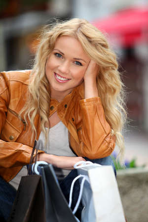Trendy beautiful woman in town with shopping bags photo