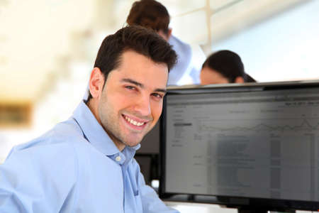 banker: Smiling trader in front of desktop computer