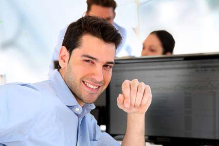 Smiling trader in front of desktop computer photo