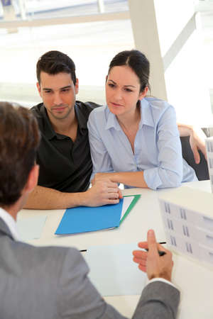 Couple in real-estate agency signing property loan contract photo