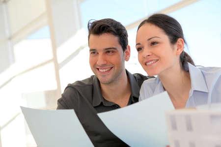 firmando: Feliz firma joven pareja de la propiedad del contrato de compra