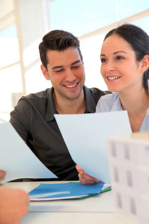 buying: Happy young couple signing property purchase contract