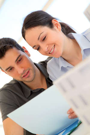 property agent: Happy young couple signing property purchase contract
